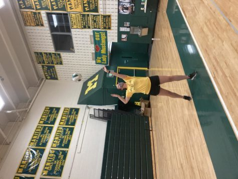 Anna Conrad practices her serve as she helps coach at a Manitou Springs volleyball practice.
