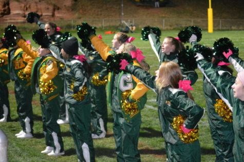 Manitou Springs High School cheerleaders, get the crowd involved in cheering on the football team at Richardson Field, Friday, October 15, 2021.  Many former cheerleaders watched from the stands this year.